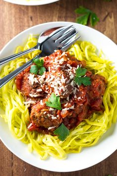 Meatballs made with chicken sausage, ground beef, and lots of garlic, slow simmered in marinara sauce, and served over spiralized crookneck squash.