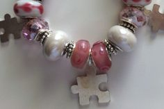 "This piece is a 7"" European style bracelet for autism awareness. It includes white porcelain beads, pink faceted beads, white glass with pink hearts to show your love of someone special , antique silver spacer beads with I love mom on them, pink swirl glass beads, and two size puzzle pieces for autism awareness. Available on my Etsy store... RomansHope $30"