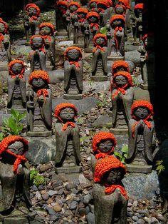Jizo - guardian deities for the spirits of miscarried children, wearing baby caps and bibs. Daien-ji, Tokyo, by Tohru Nishimura.