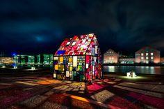 """Kolonihavehus -  Tom Fruin (1974). Tom is een kunstenaar uit New York. Het Kolinihavehus is """"Kolonihavehus"""" was het eerste stuk in Fruin's Icon-serie. De serie vertegenwoordigd aangespoelde, hergebruikte en gerecycleerde materialen gebruikt worden. Tom Fruin maakte in samen werking met Coreact dit glas-in-lood huisje (de raampjes zijn van plexiglas) dat staat voor de Koninklijke Deense Bibliotheek in Kopenhagen in Denemarken. Mooi om samenwerking van glas, kleur en licht."""