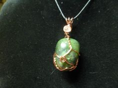 This is a Jade Wrapped with Antique Copper Non-tarnish wire. The Necklace is about 2 inches from the base of the stone to the top of the wire cord loop. Comes with cord and mesh bag to protect the necklace, to be worn as a necklace.