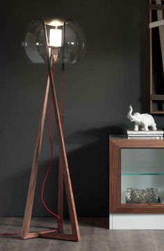 Compass by Andrea Lucatello Compass Floor lamp in natural Canaletto walnut with graphite details. Clear glass shade and red cord.