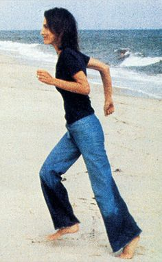 Jackie's sister, Lee Radziwill in bell bottom blue jeans on the beach, no doubt in East Hampton.