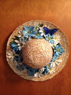 Straw hat with blue and white flowers.