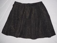 TARA JARMON. Jupe courte à plis larges. Noire irisée ( avec fils d'argent ). Acrylique