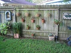Vertical Garden...hanging pots on fence.