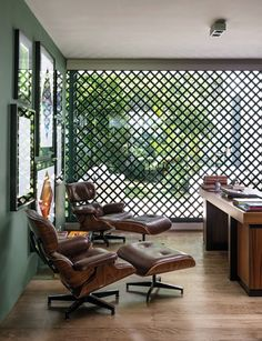 SP- Arquiteto Michel Safatle #modern (Uma porta de treliça separa o jardim, assinado pelo paisagista Rodrigo Oliveira, do home office, composto por duas poltronas Eames Lounge, de Charles e Ray Eames, e uma escrivaninha de Etel Carmona, da Etel)