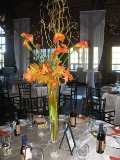 Tall wedding centerpiece of orange calla lilies, curly willow and preserved oak leaves in a tall pilsner vase