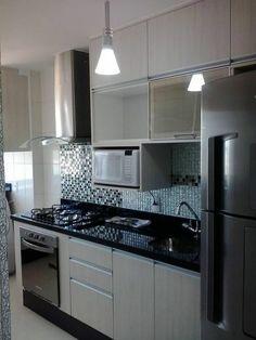 quelle couleur pour les murs d'une cuisine sur un espace restreint, avec mosaïque en bleu et vert au dessus du lavabo, plan de travail noir, luminaire minimaliste style industriel