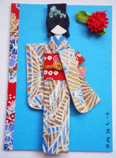 NFT.  Hand-folded Japanese paper doll mounted on card stock, card embellished with yuzen washi and handmade fabric flower.  Materials: Kimono (embossed yuzen washi); obi (yuzen washi); viscose cord on obi; hair decor (nail sticker).