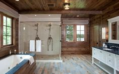 Another view of the above bathroom shows the large wood enclosed soaking tub and the large shower enclosure with dual shower heads and white subway tile.