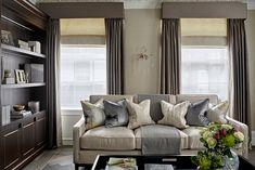 Neutral, calm, luxurious main reception, living room, lounge of grade-listed Knightsbridge townhouse. 3-seater sofa, tray coffee table, dark wood joinery with brass detailing. Hardwood herringbone flooring with trim detail. Wall sconce in brass and glass. Coffee table styling