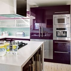 12 Kitchens with Color: An aubergine kitchen might take some getting used to. This one from the pages of British mag House to Home mixes it with plenty of stainless steel and glass, plus a pale, watery blue backsplash.