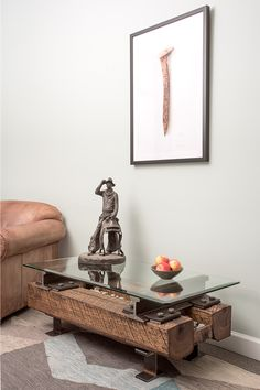 Reclaimed steel and solid wood rectabular coffee table with bronz cowboy on top and railroad spike print from Rail Yard Studios