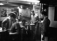Teenagers trying to work the subway turnstiles with slugs instead of tokens, 1958.