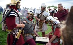 Reenactor's portraying soldiers from the Imperial Roman army play a Roman board game