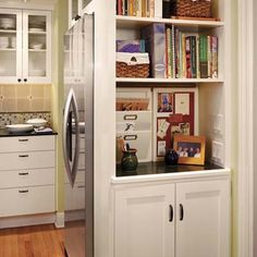 cook book shelves at side of framed-in refrigerator, from counter to ceiling, instead of a plain, boring wall