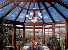 This traditional dining room is enclosed in a wood and glass atrium with a panoramic view of a rooftop garden and an elegant, white ceramic chandelier.