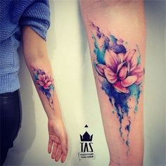 Arm Tattoo with Watercolor Lotus Flower Design.