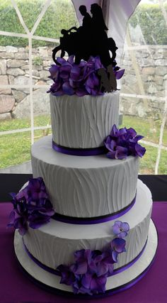 Three tier buttercream wedding cake, iced with textured light grey vanilla buttercream and decorated with black and purples ribbons as well as silk purple hydrangeas, delivered at the Moonstar Manor in Elizabethtown PA