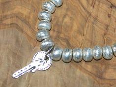 Bracelet couleur argent avec brelogue clé. Elastique pour s'adapter à tous les poignets.