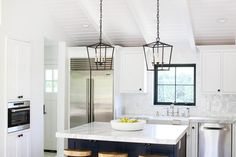 Well appointed white and navy kitchen boasts Darlana 4 Light Lanterns hung from a shiplap vaulted ceiling hangs over a blue kitchen island donning a white and gray marble countertop seating three Wisteria Smart & Sleek Stools.