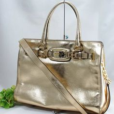 """Michael Kors Gold Metallic Hamilton Leather Tote NWT Michael Kors Pale gold purse  New with tags!! Pale Gold Metallic Leather exterior w/Gold tone hardware accents Authentic Michael Kors gold logo plate lined w/ jewels Top snap closure Dual gold metallic leather handles &crossbody chain/leather strap  Authentic Michael Kors interior fabric lining 1 large central zip compartment, 4 interior slip pockets & 1 wall zip pocket w/MK Leather patch. Measurements: 11""""H x 14.5""""L x 5.5""""D Dust bag…"""