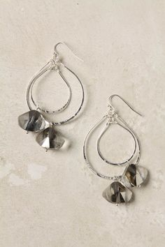 Hand-hammered silver hoops overlap in a delicate, facet-strung mobile.