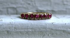 This Lovely Vintage Diamond and Ruby Band is a classic vintage design usually seen with diamonds! Crafted in 14K Yellow Gold, the design features a line of Rubies in beautiful high set Prongs. There are 7 Round Cut Natural Rubies, approximately 0.35ct total in weight, of fine quality. Just beautiful! Other Important Details: The band is a Size 6.25. The band is stamped 14K, and has been tested to be 14K White Gold. The band weighs 2.0 grams. The band is 3.0mm wide. Sizing and Engraving…