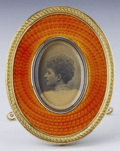 Fabergé gold and red-orange guilloché enamel frame with ivory back, with a photograph of Queen Alexandra when Princess of Wales. Workmaster Michael Perchin.