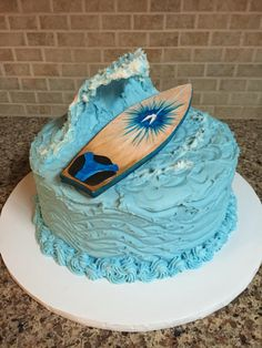 Surfboard Big Wave Grooms Cake. Red velvet cake with waves of ocean blue cream cheese buttercream frosting. Big wave cut from styrofoam cup and covered in frosting. Gumpaste surfboard is a replica of the groom's surfboard. Details painted with food gel.