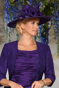 11283 (Condici) A large traditional wedding hat in a rich Damson tone. The hat has a slight up-turned asymmetric brim. The headpiece has floral and feather detailing to the front with net inlay.