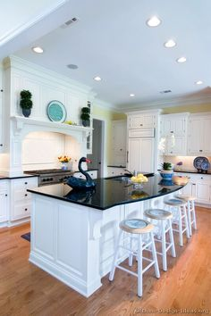 #Kitchen of the Day: A bright white kitchen with a decorative wood hood, black granite countertops, and a large island with seating... Kitchen # 1 in Traditional White Kitchens
