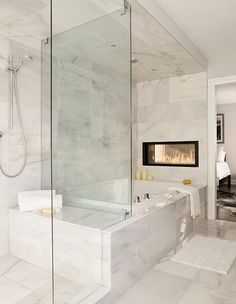 The shared wall between a master suite and the master bath is another great place for a dual fireplace. This bath was designed by none other than The Property Brothers. This page has some very useful information about home design and decor. Modern Bathtub, Modern Bathroom, White Bathroom, Master Suite Bathroom, Paint Bathroom, Zen Bathroom, Contemporary Bathrooms, Bathroom Cabinets, Bathroom Vanities