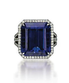 A TANZANITE AND DIAMOND RING  Set with a cut-cornered rectangular-cut tanzanite, weighing approximately 23.26 carats, to the pavé-set diamond openwork gallery and triple hoop, mounted in gold