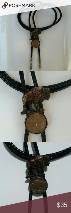 "Authentic Buffalo Head Nickel Bolo Tie Authentic Buffalo Head Nickel & Black Braided Cord Bolo Tie  Item Description - Authentic Buffalo Head Nickel   - Black braided cord  - Brass tone Buffalo  - Silver tone ends - Length 18"" or 36"" total - Note: Some wear to brass tone on buffalo  This item is used and may have some knicks or scratches. Please review all photos and ask any questions prior to purchasing. Also, unless noted I am unsure of the type of materials used. Thank you! Freddies Find…"