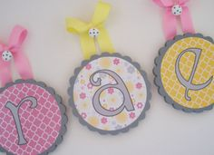 """Scallop Edge Round Wood Nursery Wall Letters - Pink, Yellow and Grey """"Raegan"""". $14.00, via Etsy."""
