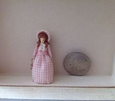 """unknown artist - Measures 1-1/4"""" T Hand sculpted doll dressed in pink gingham with pink silk ribbon carrying a tiny handbag.     From the 1980's"""