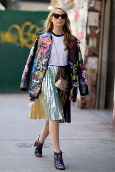 Street Style_ decorative jacket layered over tee and metallic pleated skirt accessorised with tiny purse & heeled ankle boots || Saved by Gabby Fincham ||