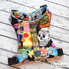 Dog Harness Sugar Skulls in Black So fun and colorful! This is our Day of the Dead cotton fabric print with black, the same fabric as our Sugar Skull but with a black background. I Love these skulls! It is adorned with metallic ribbon down the center back covering the webbing that holds