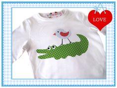Ein niedliches Kindershirt -langarm- in weiß.Darauf wurde ein lustiges Krokodil mit einem Piepmatz genäht. Dieses Shirt wurde aus Baumwolle gefert...