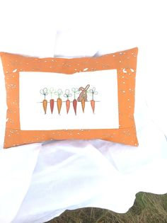 "Embroidered/quilted Cushion/Pilow : Bunny's Harvest    Everything I make is my ""favourite"" but I do really love Bunny's Harvest!    This pillow is embroidered and then quilted on lovely, soft cotton and bordered with a vibrant organic cotton in carrot orange (what else! :-)) which features tiny 'lollipop trees' and teeny tiny quail.The embroidery is in a modern 'sketch' style and shows Mr Bun getting ready to harvest his first carrot of the season.    it has an envelope closure, finished…"