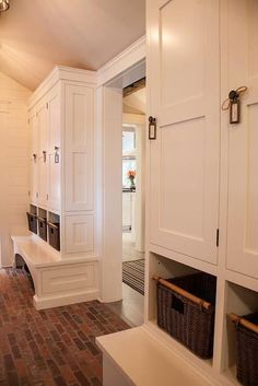 Stunning mud room with red brick floors and shiplap paneled walls alongside built-in white lockers with storage cubbies and built-in benches flanking entryway.
