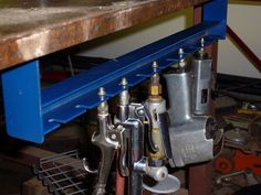 Under bench air tool holder. Screws under workbench. Keeps dust out of tips of fittings.  Materials and Tools: Tools are band saw, drill motor, hacksaw, file, vise and welder. Material is all steel. Angle 1 1/2 X 1/8. Slotted part is 1 1/2 X 1/8. And the ends are 2 X 1/8.  Contributed by: T. Roberts.  To find and share additional welding project ideas & plans, visit: www.Millerwelds.com/interests/projects/