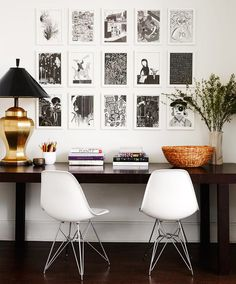 Black and white gallery wall above work desk with gold lamp, woven bowl, and stacked books