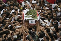 Mourners carry the casket of activist Ahmed Ismail al-Samadi, 22, during his politically charged funeral procession Friday, April 13, 2012, in Salmabad, Bahrain. Clashes between anti-government protesters and riot police erupted at the end of the funeral, which was delayed more than a week because of a dispute over his death certificate. (AP Photo/Hasan Jamali)