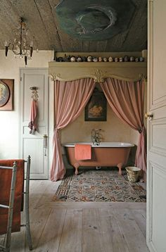 What a fabulous look for a rustic bathroom - the drapes are a lovely touch and check out that tiled flooring!
