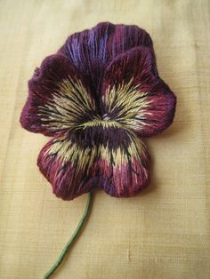 Margaret Dier Embroidery. Stumpwork long and short silk shaded pansy brooch. The petals were all embroidered individually with an edging of wire . They were then cut out and the edges turned under.