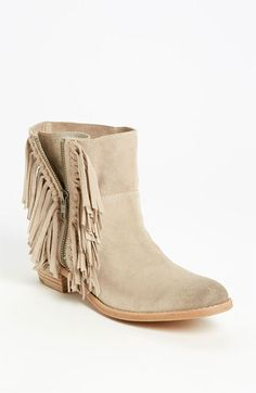 Flirty fringe frames the zipped gore of a Western-vibe boot in an abbreviated silhouette.