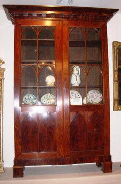 A quality Mahogany & Mahogany Veneer New York Gothic Revival Bookcase in the classical taste, with Gothic tracery on the doors and Gothic panels beneath the glass.